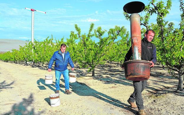 Rafael Jiménez, con botes de parafina, sigue a uno de sus empleados, que carga una estufa de gasoil. / C. CABALLERO